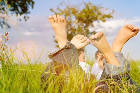 Happy couple lying on a meadow in summer, only feet to be seen photo