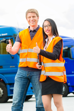 forwarder: Logistics - proud driver or forwarder and female coworker with tablet computer, in front of trucks and trailers, on a transshipment point, its a good and successful team