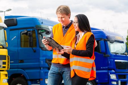 delivery driver: Logistics - proud driver or forwarder and female coworker with tablet computer, in front of trucks and trailers, on a transshipment point, its a good and successful team