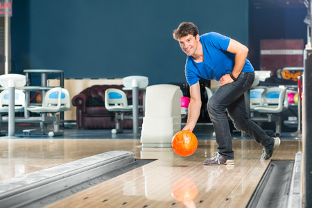 bowling alley: Young man in bowling alley having fun, the sporty man playing a bowling ball in front of the tenpin alley
