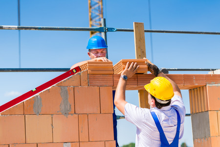 Two Bricklayer or builder or worker build or bricklaying or laying a stone or brick wall on construction or building site photo