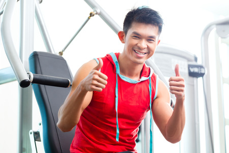 machine man: Asian Chinese man having fitness training or workout in gym doing sport to build up muscle on a weight machine