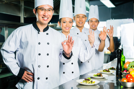 keuken restaurant: Aziatische Chef-kok in restaurant keuken koken en afwerken van gerechten