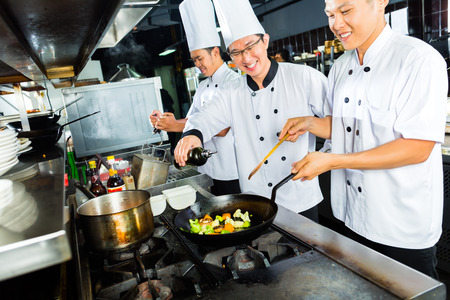 Chefs in Asian Restaurant or Hotel kitchen cooking and finishing dishes photo
