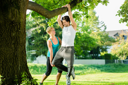 pullups: Young woman and personal trainer exercising chins or pull ups in City Park under summer trees for sport fitness