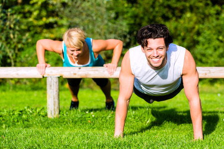 outdoor training: Young man and woman or personal trainer exercising pushups in City Park for sport fitness