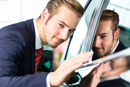 businesslike: Seller or car salesman in car dealership presenting the reflecting car paint of his new and used cars in the showroom Stock Photo