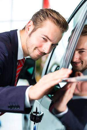 Vendeur ou vendeur de voitures dans la concession automobile présentant la peinture de voiture reflétant de ses véhicules neufs et usagés dans la salle d'exposition