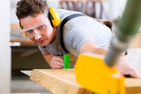 ear protection: Carpenter working on an electric buzz saw cutting some boards, he is wearing safety glasses and hearing protection for workplace safety