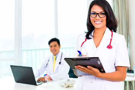 professional practice: Asian doctor and nurse working in medical office or practice Stock Photo