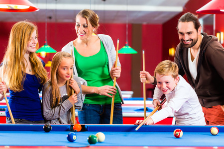 center table: Family playing together billiard with queue and balls on pool table  Stock Photo
