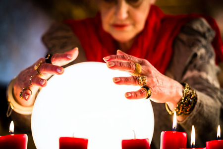 Female Fortuneteller or esoteric Oracle, sees in the future by looking into their crystal ball during a Seance to interpret them and to answer questions Stock Photo