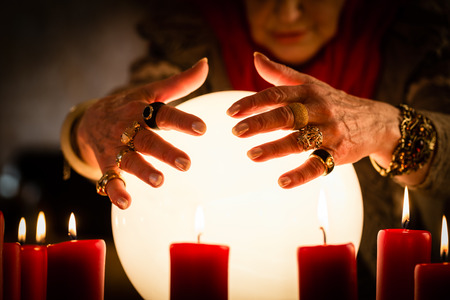 Female Fortuneteller or esoteric Oracle, sees in the future by looking into their crystal ball during a Seance to interpret them and to answer questions 版權商用圖片
