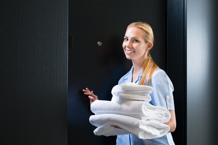 room service: Hotel room service - young chambermaid standing in front of a room door in a suite with fresh towels