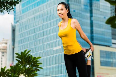 indonesian woman: Deportes urbanos - mujer indonesia asi�tica haciendo gimnasio en la ciudad en un hermoso d�a de verano de estiramiento antes de correr