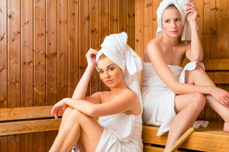 Two Women in wellness spa relaxing in wooden sauna Stock Photo - 26194268