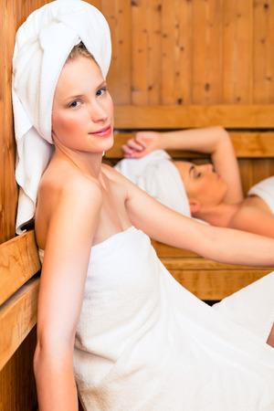 Two Women in wellness spa relaxing in wooden sauna Stock Photo - 26194269