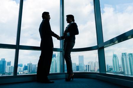 business asia: Gente di affari asiatica stretta di mano per sigillare affare di fronte skyline della citt�