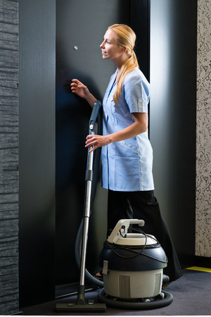 room service: Hotel room service - young chambermaid standing in front of a suite door in a hotel with a vacuum cleaner to clean the room