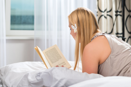 kingsize: Young woman lying in the bed of a hotel room reading a book, she is on vacation