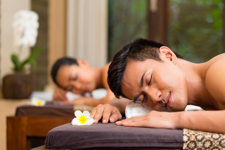 Indonesian Asian couple man and woman in wellness beauty spa having aroma therapy massage with essential oil, looking relaxed photo