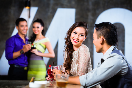 Dvě asijské Mladý a pohledný Mladí lidé páry flirtování a pití v baru v luxusní a efektní noční klub