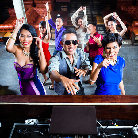 Asian party people men and women partying on the dance floor in fancy night club photo