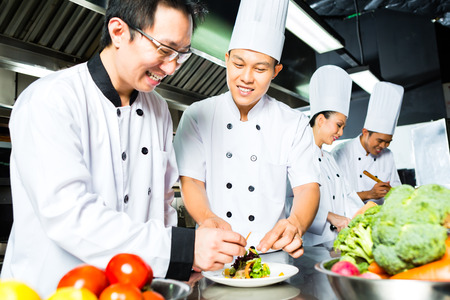 asian chef: Asian Indonesian chef along with other cooks in restaurant or hotel commercial kitchen cooking, finishing dish or plate