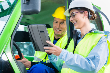 Construction worker in construction machinery discussing with engineer blueprints on pad or tablet computer on site Stock Photo