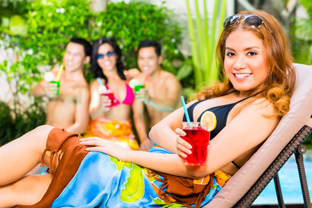 Asian friends partying and drinking fancy cocktails at hotel or club pool party photo