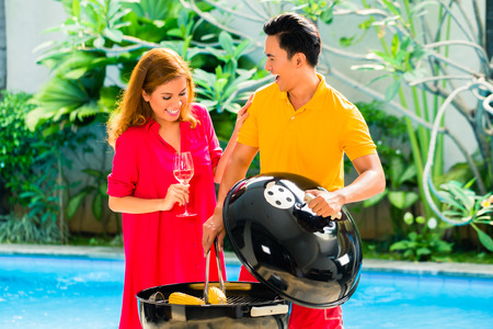 Asian handsome couple drinking wine and having barbecue party or BBQ outside at the pool with grilled corn cobs photo