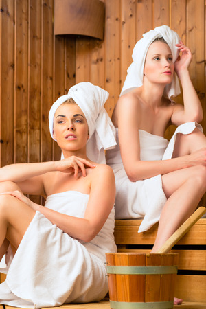 Two Women in wellness spa relaxing in wooden sauna Stock Photo - 26194135