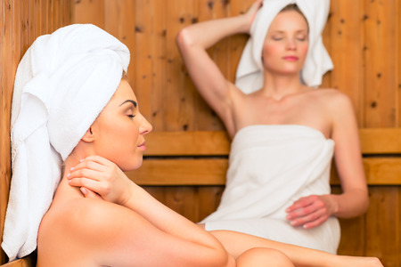 Two Women in wellness spa relaxing in wooden sauna Stock Photo - 26194137
