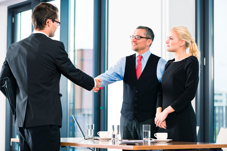 Business - young man in job interview for hiring, welcomes, Boss or Senior and his female Assistant in their office photo