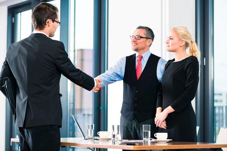 entrevista de trabajo: De negocios - hombre joven en la entrevista de trabajo para la contratación, da la bienvenida, jefe o mayor y su asistente femenina en su oficina