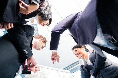 deal in: Asian business people in group structuring deal on flipchart