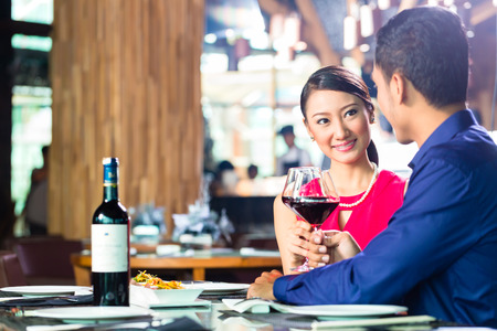 Asian couple having dinner and drinking red wine in very fancy restaurant with open kitchen  photo