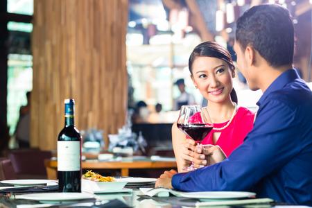 Asian Paar mit Abendessen und trinken Rotwein in sehr schickes Restaurant mit offener Küche