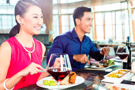 Asian people having dinner and drinking red wine in very fancy restaurant with open kitchen