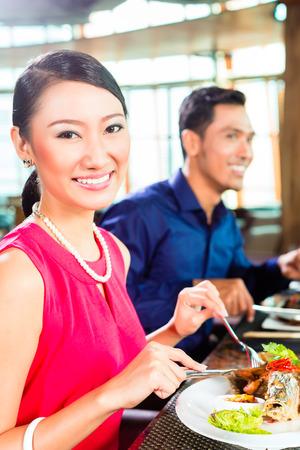 Asiaten mit Abendessen und trinken Rotwein in sehr feinen Restaurant mit offener Küche Standard-Bild