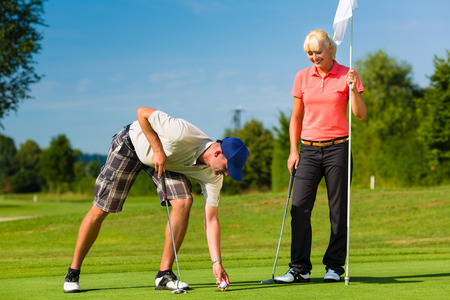 golf cap: Young sportive couple playing golf on a golf course, he takes the ball from the hole