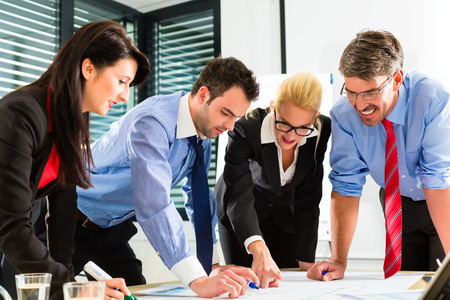 corporate meeting: Four professionals in the office in business clothes when planning a strategy for the future of the business Stock Photo