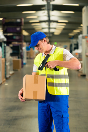 Warehouseman with protective vest and scanner, scans bar-code of package, he standing at warehouse of freight forwarding company photo