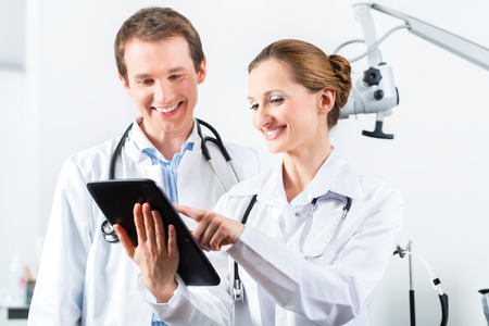 Doctors - male and female - discussing test reports that show on their tablet Computer photo