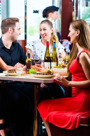 Freunde oder Paare, essen Fast Food und trinken Bier und Wein in einem amerikanischen Fast-Food-Diner
