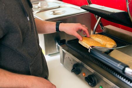 casse-cro�te: Hotdog - sympathique vendeur et frais ingr�dients dans un snack-bar de la restauration rapide