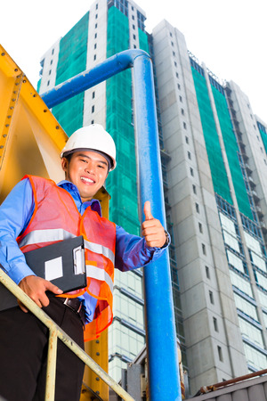 tallyman: Chinese construction worker or supervisor or architect with clipboard on a building site in Asia