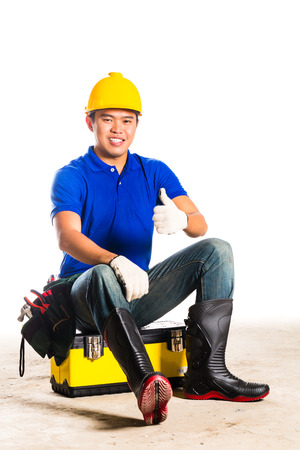 tallyman: Indonesian Asian builder or construction worker with helmet and  tool belt sitting on tool box Stock Photo