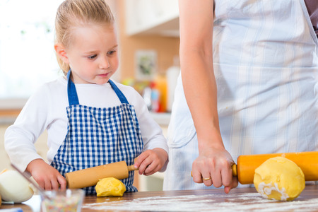 contribute: Family home baking - Mother and daughter baking cookies together at home Stock Photo