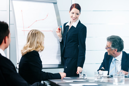 Business - presentation within a team in office, a colleague is standing on the flipchart photo